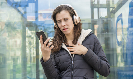 jealousy and suspicion in the cell phone, couple problems, adult woman looking at suspicious messages on the phone while on the street listening to music with headphones Banque d'images