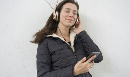 Brown-haired woman listening to music with the mobile. enjoying music with golden and white helmets on the street in winter Banco de Imagens