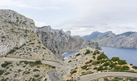 Wide view of Cape Formentor viewpoint with blurred tourists and coastline in Mallorca Stock Photo