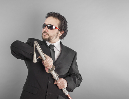 Businessman with sword isolated on grey, aggressive lawyer with Japanese sword, defiant and defensive attitude