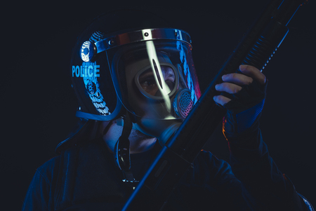Special unit policeman in a gas mask and shield, isolated on black Stock Photo