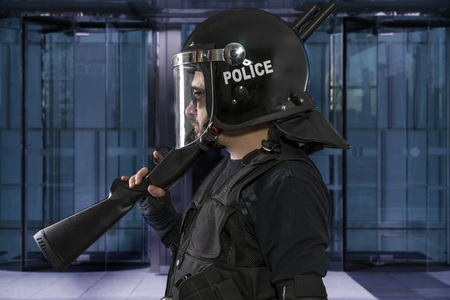 police armed with riot helmet and vest in a business center protecting Stock Photo
