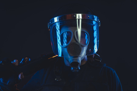 Soldier, Special unit policeman in a gas mask and shield, isolated on black