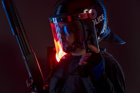 politieagent met volledige uitrusting voor anti-oproerpolitie, wetshandhaver in beschermend uniform klaar voor menigte controle geïsoleerd op zwart