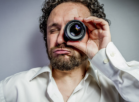 photographer with lens, man with intense expression, white shirt