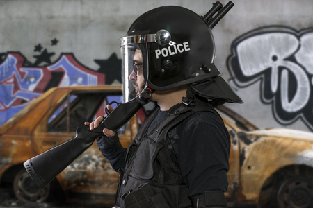 armed police with riot helmet and vest in a scene with a burnt car and riots Archivio Fotografico