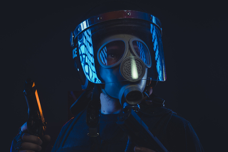 Protection, Special unit policeman in a gas mask and shield, isolated on black Stock Photo