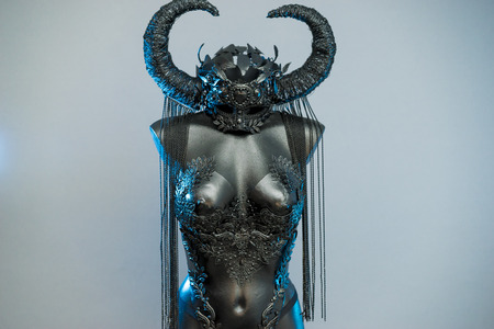 Ritual Witch. Black dress with helmet of big dark horns. pieces of metal and corset of rhinestones and lace Редакционное