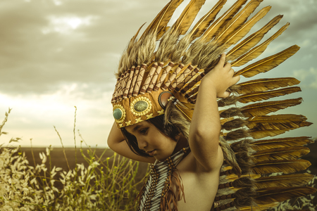 Child dressed as an American Indian at sunset, wearing an Indian feather plume and breastplate of bones. Playing next to a cereal meadow