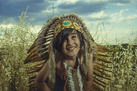 Little boy dressed as an American Indian at sunset, wearing an Indian feather plume and breastplate of bones. Playing next to a cereal meadow with happy faces Stock Photo