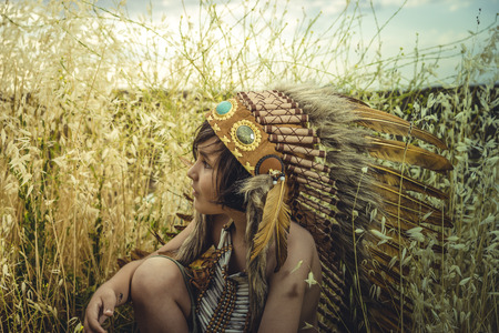 Child dressed as an American Indian at sunset, wearing an Indian feather plume and breastplate of bones. Playing next to a cereal meadow with happy faces Stock Photo