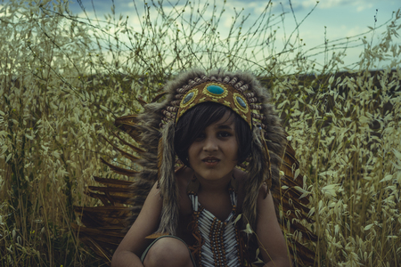 Boy dressed as an American Indian at sunset, wearing an Indian feather plume and breastplate of bones. Playing next to a cereal meadow with happy faces