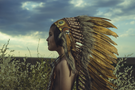 Summertime, Child playing at sunset dressed as an American Indian, wearing an Indian feather plume and breastplate. Field of wheat and nature