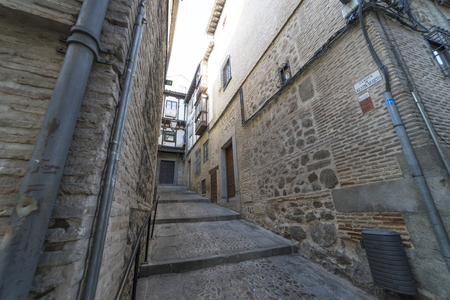 Medieval cobbled and stepped street with flowery balconies and public lighting lamps in the city of Toledo. Spain Éditoriale