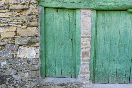 Green door, wood and stone houses in the province of Zamora in Spain Фото со стока