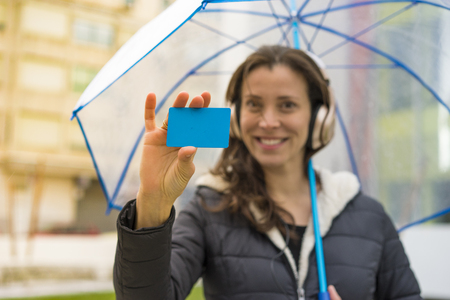 Payment, woman with bank card in hand, brunette in the street with an umbrella that goes shopping Stock Photo