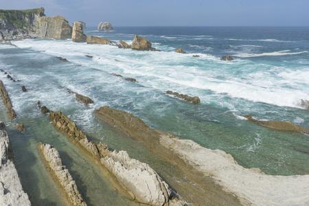 Touristic, Rocks on the beach. Dramatic view of Playa de la Arnia, rocky coastline in Santander ,Cantabria, Spain. Stock Photo