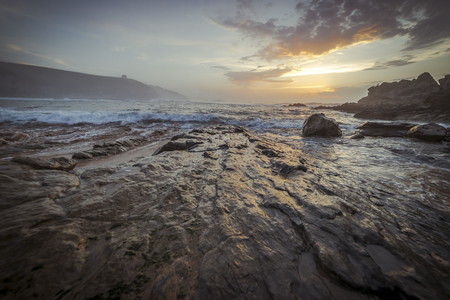 Sunset in Tagle beach. panoramic view of nice colorful huge cliff and sea on the back. Cantabria. Spain.