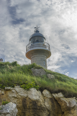 Summer, coastal lighthouse on the Playa de los Locos in Cantabria, Spain Stock Photo