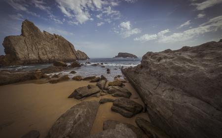 Beach with rocks in summer. Playa de la Arnía in Santander, Spain