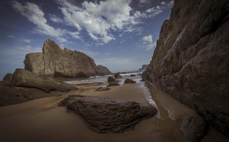Travel, Beach with rocks in summer. Playa de la Arnía in Santander, Spain