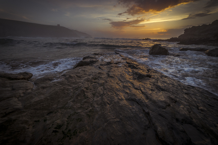 Seascape, Sunset in Tagle beach. panoramic view of nice colorful huge cliff and sea on the back. Cantabria. Spain.