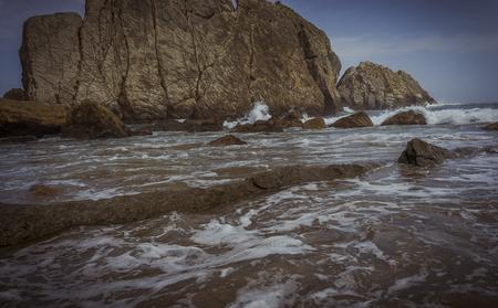Ocean, Beach with rocks in summer. Playa de la Arnía in Santander, Spain