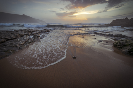 Calm, Sunset in Tagle beach. panoramic view of nice colorful huge cliff and sea on the back. Cantabria. Spain. Stock Photo