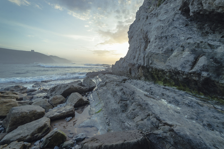 Travel, Sunset in Tagle beach. panoramic view of nice colorful huge cliff and sea on the back. Cantabria. Spain.