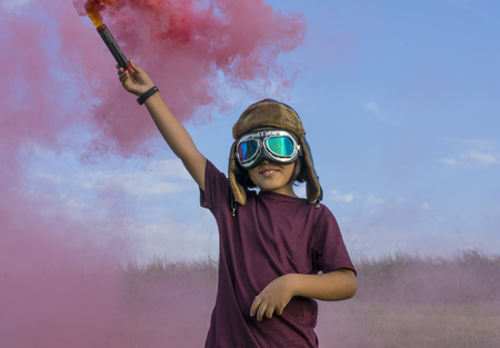 Airborne, Little boy wearing helmet and aircraft googles standing on a green field with colorful smoke, pretending to be a pilot