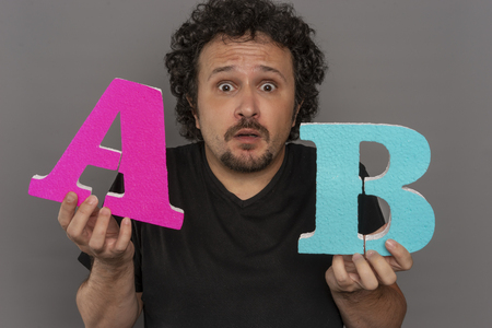Market, conversion funnel, A  B test in marketing and online advertising. Brunette man holding colored letters A and B in hands with face expressions