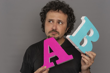 Website conversion funnel, A  B test in marketing and online advertising. Brunette man holding colored letters A and B in hands with face expressions Stock Photo