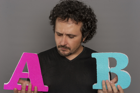 Comparison, conversion funnel, A  B test in marketing and online advertising. Brunette man holding colored letters A and B in hands with face expressions