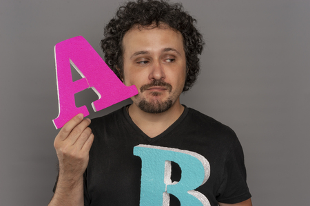 Testing, conversion funnel, A  B test in marketing and online advertising. Brunette man holding colored letters A and B in hands with face expressions