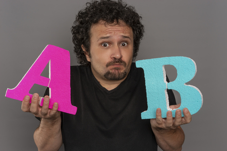 Optimize, conversion funnel, A  B test in marketing and online advertising. Brunette man holding colored letters A and B in hands with face expressions Stock Photo