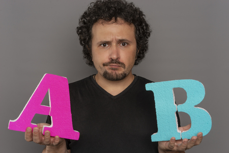 conversion funnel, A  B test in marketing and online advertising. Brunette man holding colored letters A and B in hands with face expressions
