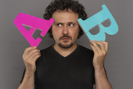 Choice, conversion funnel, A / B test in marketing and online advertising. Brunette man holding colored letters A and B in hands with face expressions