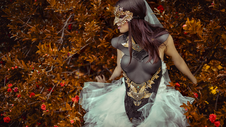 mysterious woman dressed in white with mask of leaves in copper and gold color in a garden in autumn