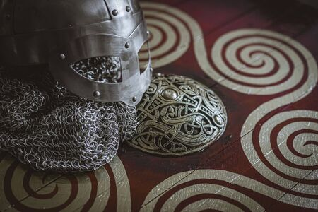 Triskel, Vikings, viking helmet with chain mail on a red shield with golden shapes of sun, weapons for war Фото со стока