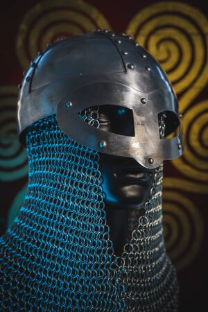 Traditional Vikings, viking helmet with chain mail on a red shield with golden shapes of sun, weapons for war Standard-Bild