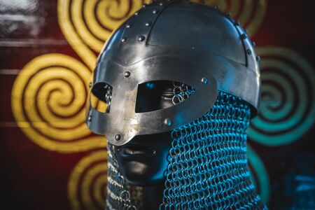 Soldier Viking helmet with chain mail of iron on red shield of wood and golden triskel Standard-Bild