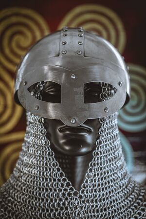 Weapons Viking helmet with chain mail of iron on red shield of wood and golden triskel