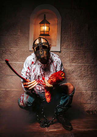 Zombie, Halloween holiday celebration, cosplay. Man demon on castle background. Satan with chains, red blood. Hell, death, evil, horror concept. Devil with bloody stains