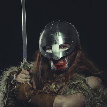 Viking scandinavian warrior with sword and wild skins. leather and bib overalls, metal helmet
