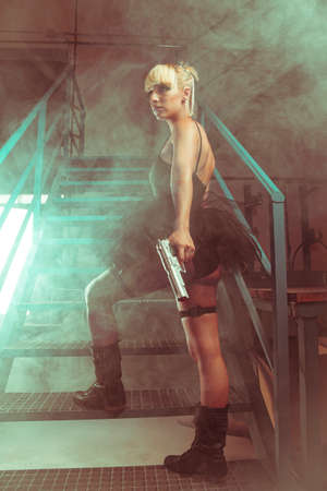Blonde girl with pistols in an abandoned factory. cosplayer, action and dangerous woman Standard-Bild