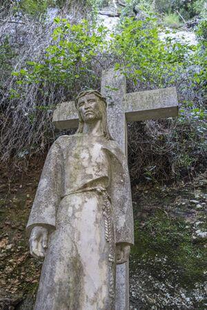 Jesus Christ cross, sculpture of jesus on the cross made in stone in the monastery of Montserrat in Barcelona, Spain 写真素材
