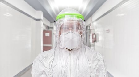 hospital corridor with male nurse wearing protective face mask, glasses and sanitary mask. coronavirus concept and hospital treatment