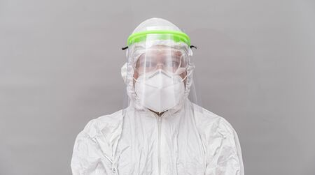 Nurse with protective face mask, glasses and sanitary mask. coronavirus and treatment concept on gray and neutral background