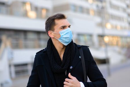 Portrait of young handsome businessman with face mask in quarantine of flu. Photo in caffee with laptop, mobile phone. Coronavirus pandemic.