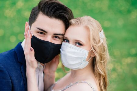 Young loving couple walking in medical masks in the park during quarantine on their wedding day. Coronavirus, disease, protection, sick. Europe celebration canceled.